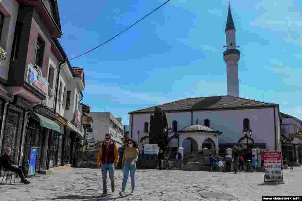 A couple with protective masks walk in front of the Murat Pasha mosque in Skopje on April 23. The Islamic Religious Community of North Macedonia has decided to close all mosques during Ramadan to prevent the spread of the coronavirus.