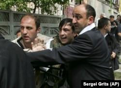 """Охранники уводят президента Михаила Саакашвили (в центре) в укрытие после того, как была объявлена воздушная тревога. Гори, 11 августа 2008 года (период """"пятидневной войны"""")"""