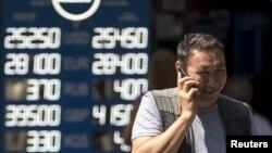 Мужчина у обменного пункта валют с новыми курсами валют. 20 августа 2015 года.