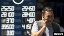 Мужчина рядом с обменным пунктом в Алматы после решения правительства о переходе к «свободно плавающему обменному курсу». Алматы, 20 августа 2015 года.