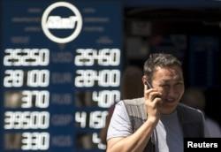 Валюта бағамы жазылған табло жанында телефонмен сөйлесіп бара жатқан адам. Алматы, 20 тамыз 2015 жыл. (Көрнекі сурет)