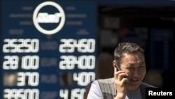 """Мужчина рядом с пунктом обмена валют в день, когда власти объявили о переходе к политике """"свободно плавающего обменного курса"""". Алматы, 20 августа 2015 года."""