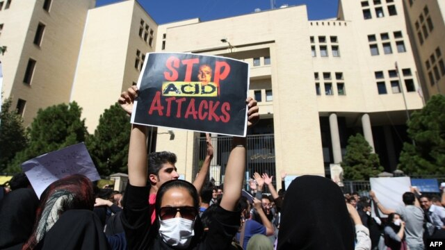An Iranian woman, hiding her face so as not to be identified, raises a placard during a protest to show solidarity with the acid-attack victims, in front of the judiciary building in Isfahan on October 22.
