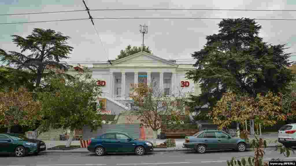 За багаторічними деревами розташований центральний кінотеатр Севастополя – «Победа»