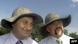 South Ossetia's Eduard Kokoity (left) and Transdniester's Igor Smirnov (wearing sun hats at an event in South Ossetia in June 2009) may no longer fit into Russia's plans for their regions.