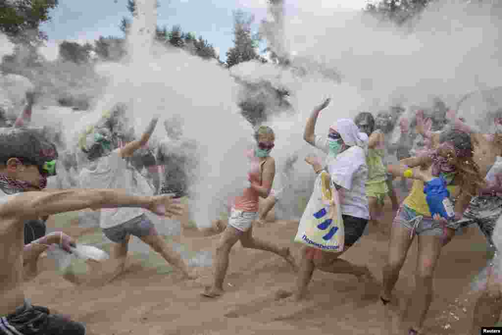 Youths throw flour at each other during a flash mob on the banks of the Dnipro River in Kyiv, Ukraine. About 100 people participated in the flash mob. (Reuters/Valentyn Ogirenko)