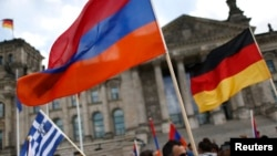 GERMANY-- Supporters hold Armenian, German and Greek flags during approval of a resolution by Germany's parliament that declares the 1915 massacre of Armenians by Ottoman forces a genocide.