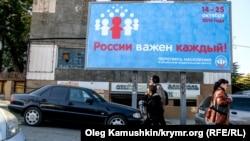 Люди на улице города Симферополя проходят мимо билборда, оповещающего о переписи населения.