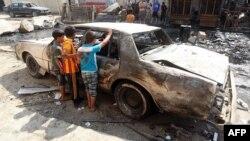 أطفال ينظرون الى حطام سيارة في موقع تفجير ببغداد