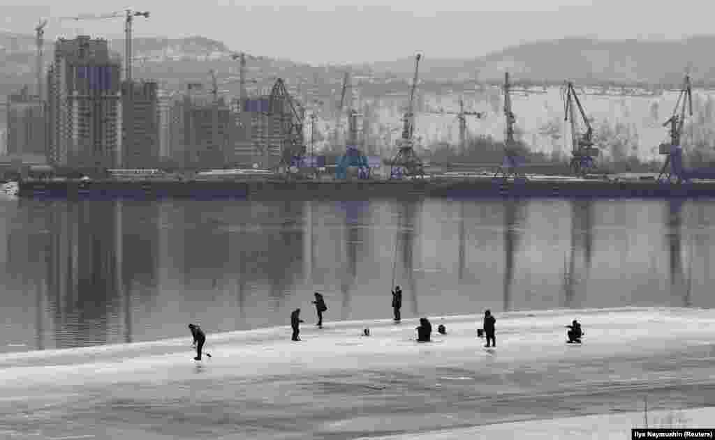Men fish on the ice-covered Yenisei River in Krasnoyarsk, Russia. (Reuters/Ilya Naymushin)
