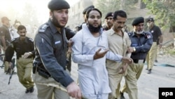 Pakistani police arrest a suspect after a suicide car-bomb attack outside a police station in Kohat on October 15.