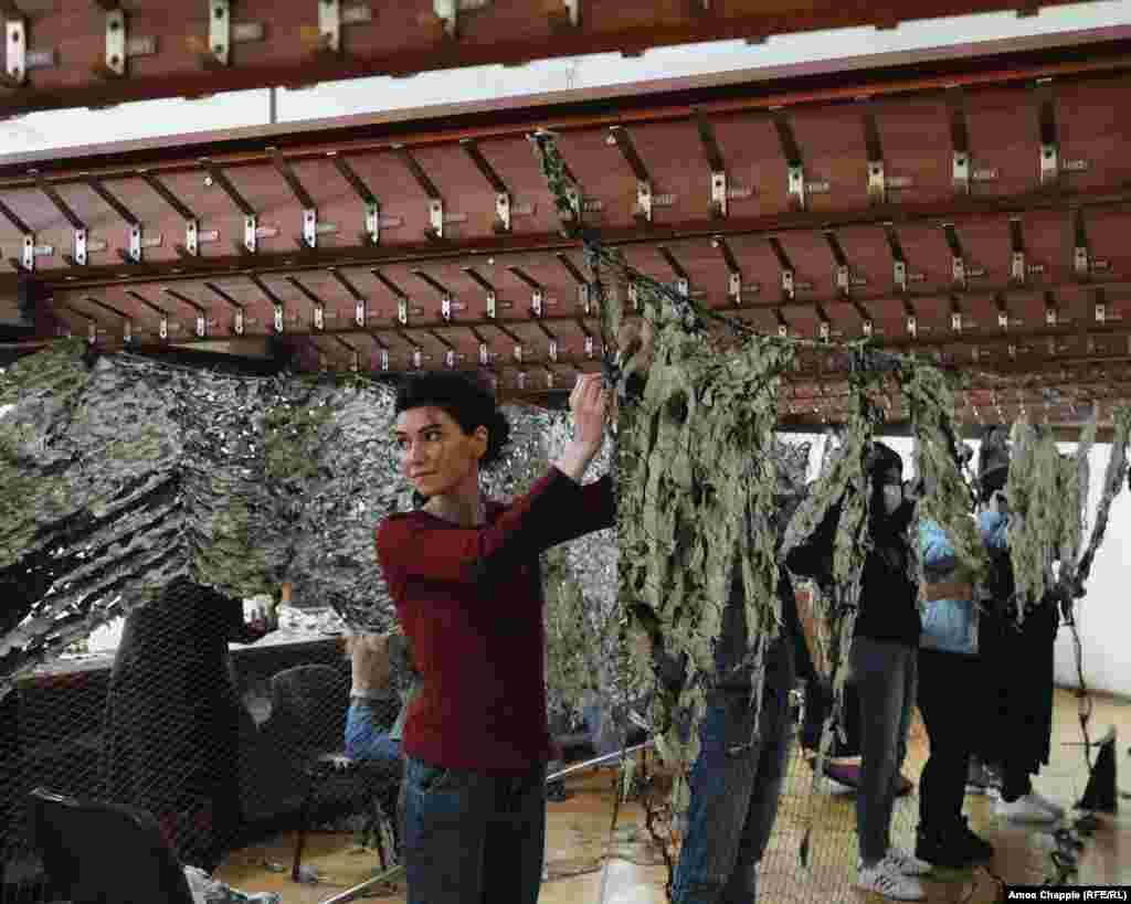 """Ева Геворгян, която е контрабасистка в Арменския национален филхармоничен оркестър, е една от много елитни музиканти, които извършват своята доброволческа дейност в същата сграда, в която обикновено изнасят своите концерти. Пред Радио Свободна Европа/Радио Свобода Геворгян казва, че на фронта се нуждаят спешно от камуфлажна мрежа. """"Не е евтина, а[Армения] няма толкова много пари"""", казва тя."""