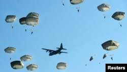 Netherlands -- Paratroopers from the United States drop by parachute from an airplane to commemorate the 70th anniversary of Operation Market Garden, in Groesbeek, in the east of The Netherlands, 18 September 2014.