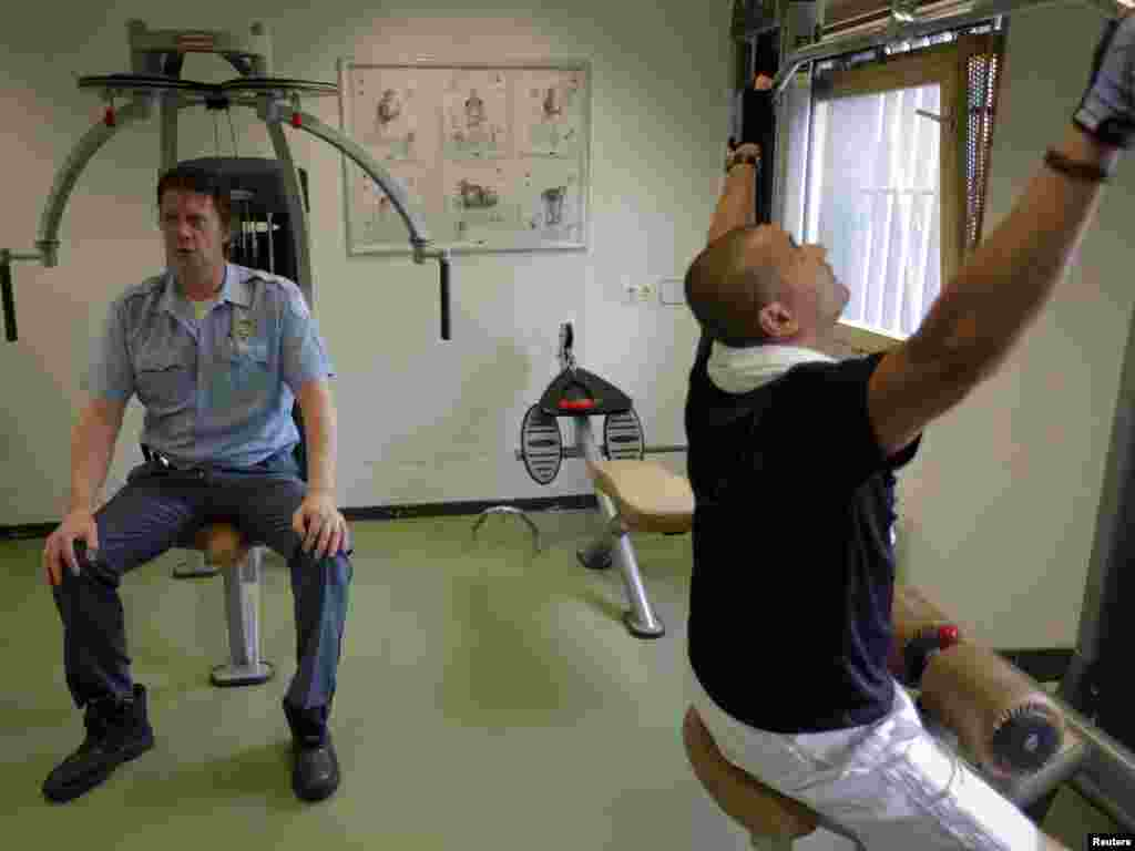 Security guards exercise at a gym shared with those accused of war crimes.