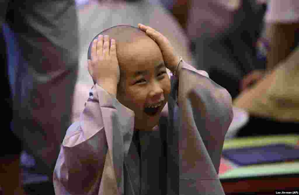 A young South Korean boy touches his newly shaved head during a Buddhist service at the Jogye Temple in Seoul. (AP/Lee Jin-man)
