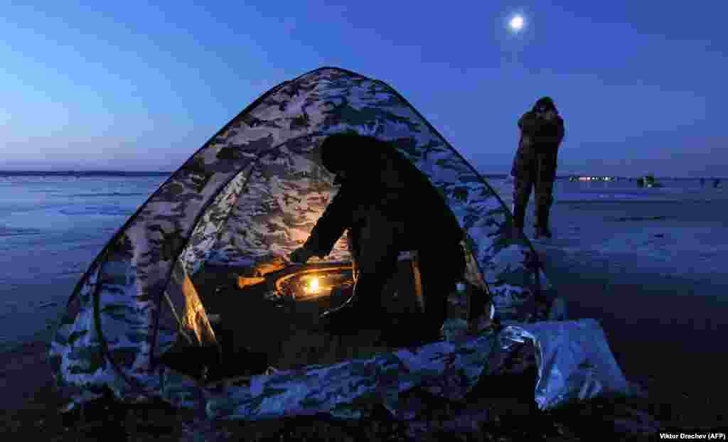 A man sits in a tent while ice fishing at sunrise on Lake Vileika, some 130 kilometers north of the Belarusian capital, Minsk. (AFP/Viktor Drachev)