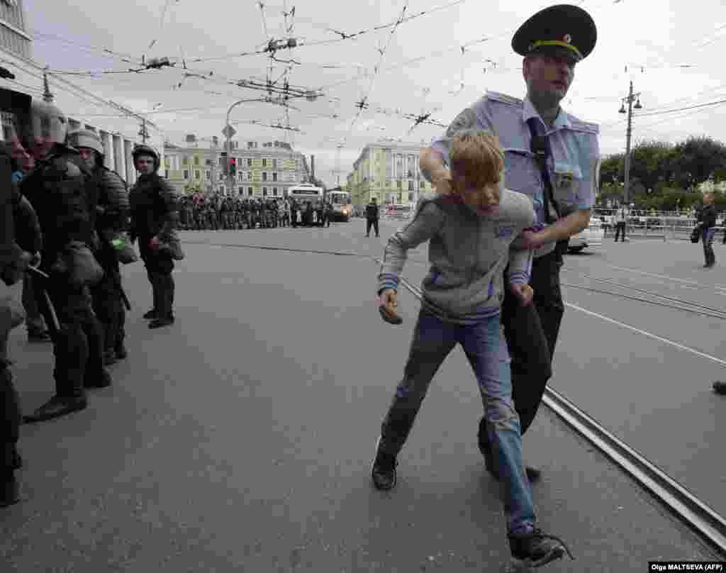 A child is led away by a police officer during a protest in St. Petersburg.