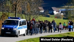 Migrants are escorted by German police to a registration center after crossing the Austrian-German border in Wegscheid near Passau, Germany in November 2015.