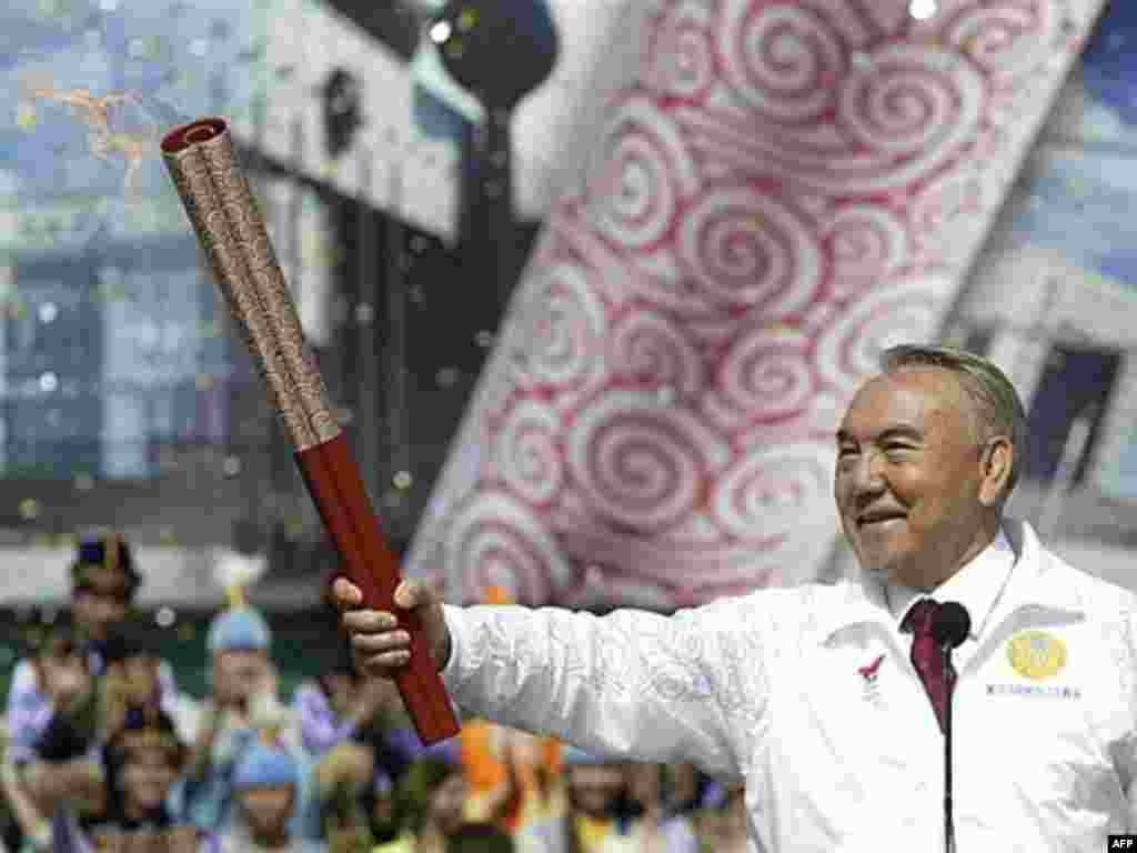 Kazakh President Nursultan Nazarbaev holds the Olympic torch at a stadium outside Almaty, the first stop after Beijing, in April 2008.