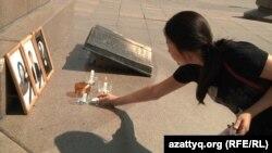 Девушка зажигает свечу в память о Жансауле Карабалаевой и двух погибших в Жанаозене нефтяниках. Алматы, 9 сентября 2011 года.