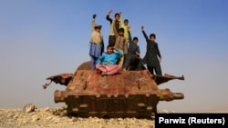 Afghan children play on Soviet-era wreckage on the outskirts of Jalalabad.