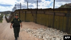 A U.S. security officer patrols along a border fence with neighboring Mexico designed to keep out illegal immigrants.
