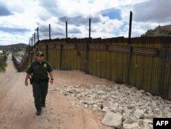 Офицер пограничной службы идет вдоль американско-мексиканской границы.
