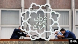 Iran -- Workers installing Tehran's Municipality logo on the top of it's Headquarter in Bahesht street in Tehran, undated.
