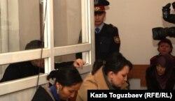 Полицейский-конвоир между подсудимым Саяном Хайровым и его женой Шынарой Бисенбаевой (справа, в хиджабе). Алматы, 7 ноября 2013 года.