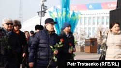 Активист Жанболат Мамай и другие инициаторы создания Демократической партии Казахстана возлагают цветы к монументу Независимости. Алматы, 16 декабря 2019 года.