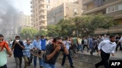 """Сторонники """"Братьев-мусульман"""" спасаются бегством после того, как полиция применила слезоточивый газ против обитателей лагеря протестующих Рабаа аль-Адавия."""
