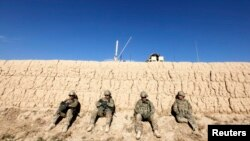 U.S. Army soldiers sit behind a wall as others search for explosives after an improvised explosive device damaged one of their armored vehicles during a road clearance patrol in Logar Province, in eastern Afghanistan. (file photo)