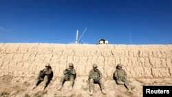 U.S. Army soldiers sit behind a wall as others search for explosives after an improvised-explosive-device blast damaged an armored vehicle during a road-clearance patrol in Logar Province in eastern Afghanistan.