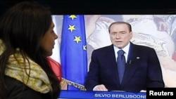 Një vajzë duke shikuar Silvio Berluskonin në ekran.(Foto nga arkivi)