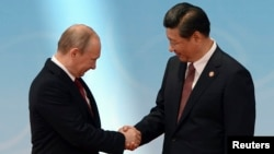 Президент России Владимир Путин (слева) с китайским коллегой Си Цзиньпином.