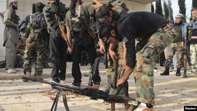 Free Syrian Army fighters prepare their weapons near the town of Atareb.