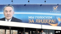 A bus passes a huge election poster of Kazakh President Nursultan Nazarbaev in Astana.