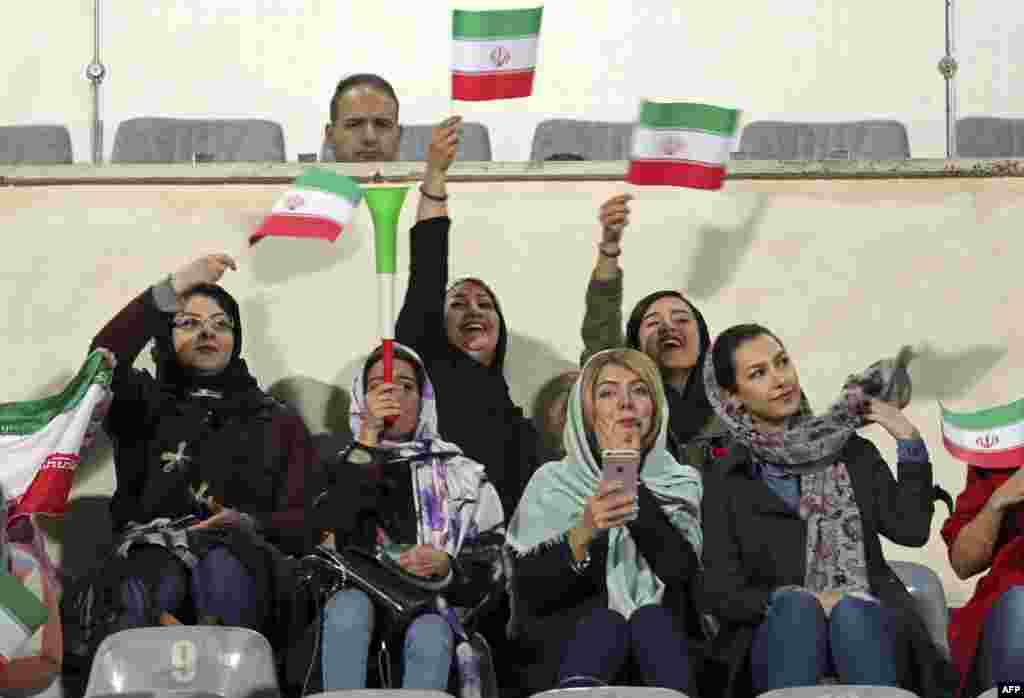 Iranian women cheer during the friendly soccer match between Iran and Bolivia at the Azadi Stadium in Tehran on October 16, where a small group of selected women were allowed to watch. (AFP)