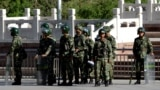 China -- Chinese paramilitary policemen stand guard on a city square in Urumqi in China's Xinjiang region on May 24, 2014. China has seen a series of incidents in recent months targeting civilians, sometimes far from Xinjiang itself, which authorities ha