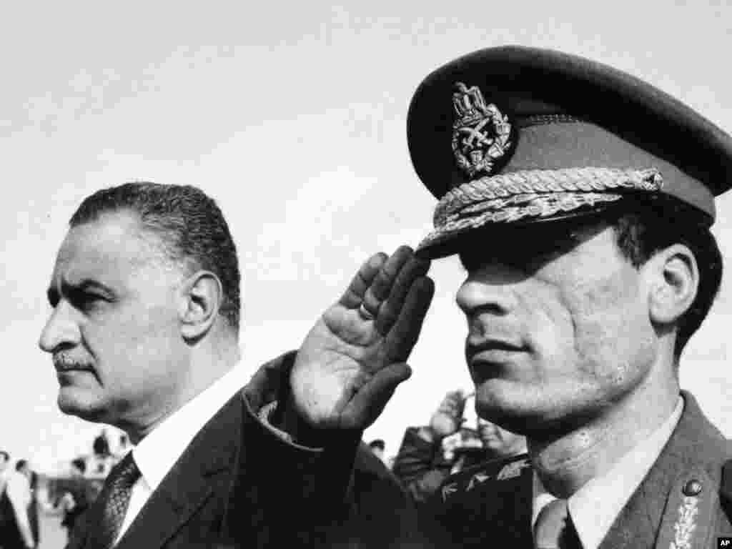 In this 1969 file photo, Qaddafi salutes as he appears with Egypt's Prime Minister Gamal Abdel Nasser, in Suez, Egypt.