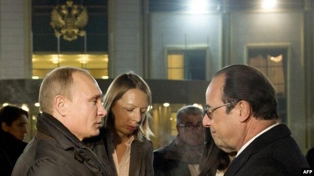 Ресей президенті Владимир Путин (сол жақта) әуежайдағы үш сағаттық қысқа кездесуден кейін Франция президенті Франсуа Олландты шығарып салып тұр. Мәскеу, 6 желтоқсан 2014 жыл.
