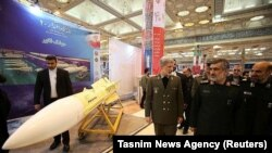 Iranian Defense Minister Amir Hatami walks (L) at a military exhibition in Tehran, Fabruary 2, 2019