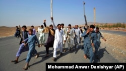 Afghans shout slogans against the government after a military operation reportedly left many civilians dead in the Rodat district of Nangarhar Province on October 24.