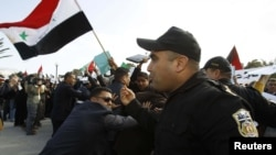 "Police clash with protesters during a demonstration against Syrian President Bashar al-Assad outside the ""Friends of Syria"" conference in Tunis on February 24."