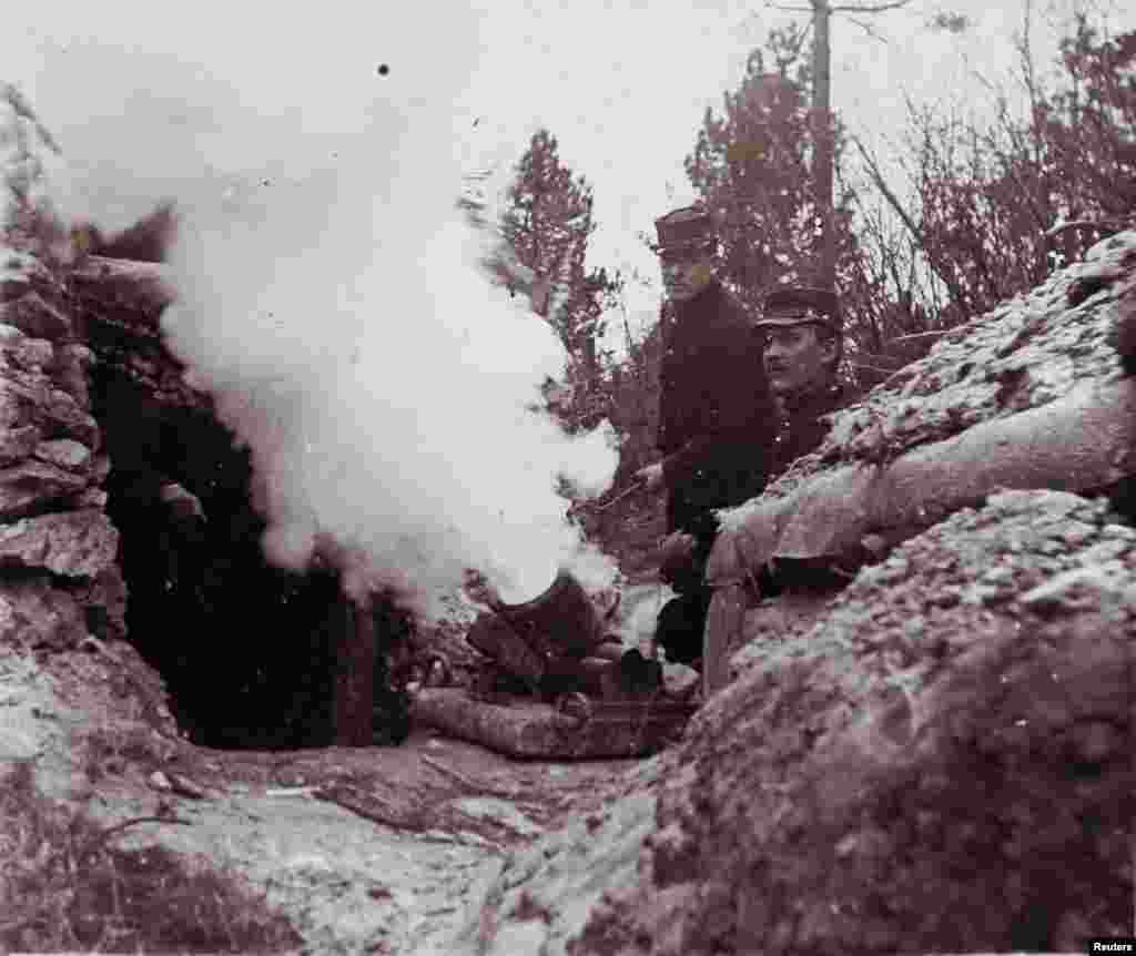 An undated photo shows French soldiers firing a 155 mm mortar from a trench on the front line, at an unknown location in France.