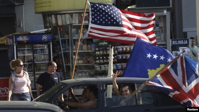 Kosovars wave the U.S., Kosovo, and U.K. flags as they celebrate in Pristina on July 22, 2010, after the World Court said Kosovo's declaration of independence was legal.