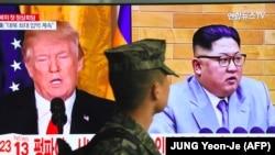 Южнокорейский солдат смотрит на изображение Дональда Трампа и Ким Чен Ына в телевизоре. Сеул, 9 марта 2018 года