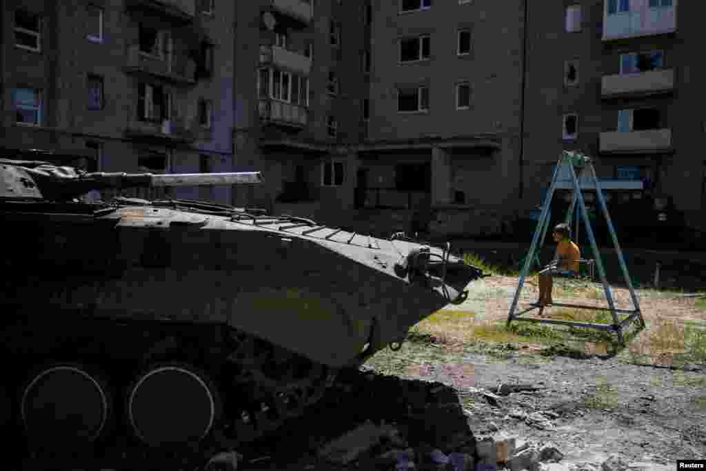 A boy sits on a swing near his building, which was damaged during fighting between the Ukrainian Army and pro-Russian separatists, as an armored personnel carrier of the Ukrainian armed forces is seen nearby in Avdiyivka, near Donetsk. (Reuters/Gleb Garanich)