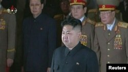 Kim Jong Un, flanked by senior military men, pays his respects to his father, the former North Korean leader Kim Jong Il, lying in state at the Kumsusan Memorial Palace in Pyongyang on December 20.