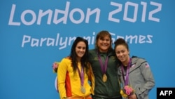 American bronze medalist Elizabeth Stone (right) joins Spanish silver medalist Sarai Gascon (left) and South African gold medalist Natalie du Toit on the podium after the women's 100-meter backstroke finals in London on August 31.